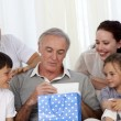 Family giving to grandfather a present - Foto Stock