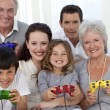 Stock Photo: Grandparents, parents and children playing video games