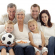 Family watching a football match at home — Stock Photo
