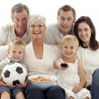 Stock Photo: Happy family watching a football match at home
