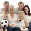 Happy family watching a football match at home — Stock Photo