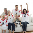 Stock Photo: Happy family watching a football match in television