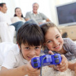 Children playing video games on floor and family on sofa — Stock Photo