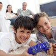 Children playing video games and family on sofa — Stock Photo #10298080