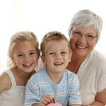 Grandmother and children saving money in a piggybank — Stock Photo