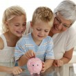 Close-up of grandmother and children saving money — Stockfoto #10298086