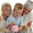 Foto de Stock  : Close-up of grandmother and children saving money
