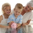 Grandmother and children saving money in a piggybank — Stockfoto