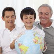 Son, father and grandfather looking at a terrestrial globe - Lizenzfreies Foto
