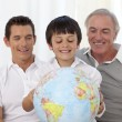 Son, father and grandfather looking at a terrestrial globe - Stock Photo