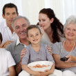 Family eating chips and watching television — Stock Photo
