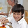 Portrait of a boy having dinner with his family - Stock Photo