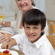 Smiling boy having dinner with his family — Stock Photo