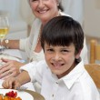 Smiling boy having dinner with his family - Stock Photo