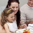 Mother and daughter eating with their family - Foto Stock