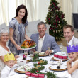 Family celebrating Christmas dinner with turkey - Foto Stock