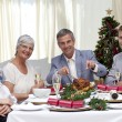 Family eating turkey in Christmas Eve Dinner - Stock Photo