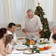 Family having Christmas dinner eating turkey - Stock Photo