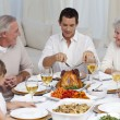 Father serving turkey to his family in a dinner — Stock Photo