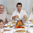 Family eating turkey and vegetables in a celebration meal — Stock Photo