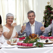 Family tusting in a Christmas dinner with white wine — Stock Photo #10298143