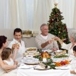 Stock Photo: Grandparents and parents tusting in Christmas dinner