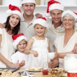 Children baking Christmas cakes in the kitchen with their family — Stock Photo