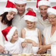 Family baking Christmas cakes and sweets in the kitchen — Stock Photo