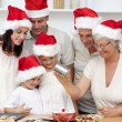 Happy family baking Christmas cakes — Stock Photo
