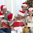 Family opening Christmas presents at home — Stock Photo #10298213