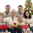 Family holding Christmas presents at home — Stock Photo