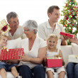 Family opening Christmas gifts at home — Stock Photo #10298234