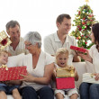 Happy family at home opening Christmas presents - Stock Photo