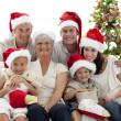 Children sitting with their family holding Christmas boots — Stock Photo #10298245