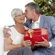 Senior man giving a kiss and a Christmas present to his wife — Stock Photo