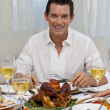 Smiling man eating turkey in Christmas dinner — Stock Photo