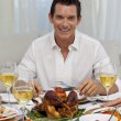 Smiling man eating turkey in Christmas dinner — Stock Photo #10298277