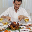 Attractive man eating turkey in Christmas dinner — Stock Photo