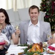 Parents toasting with champagne in Christmas dinner — Stock Photo