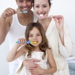 Parents and daughter cleaning their teeth in bathroom — Stock Photo