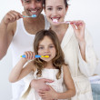 Parents and daughter cleaning their teeth in bathroom - Stock Photo