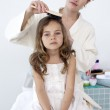 Mother brushing her daughter's hair — Stock Photo #10298324