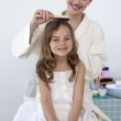 Mother doing her daughter's hair — Stock Photo #10298326