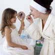 Daughter helping her mother in makeup — Stock Photo