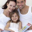 Portrait of parents and daughter reading in bed — Stock Photo