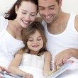 Stock Photo: Young family reading in bed