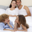 Brother and sister in bed with her parents — Stock Photo