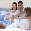 Brother and sister playing in bed with their parents — Stock Photo