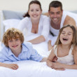 Brother and sister having fun in bed with their parents — Stock Photo