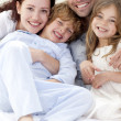 Stock Photo: Portrait of young family lying in bed